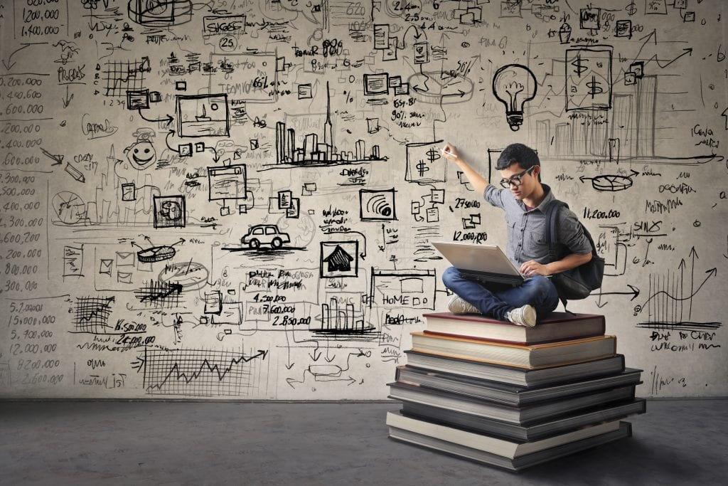 Student sitting on books developing ideas